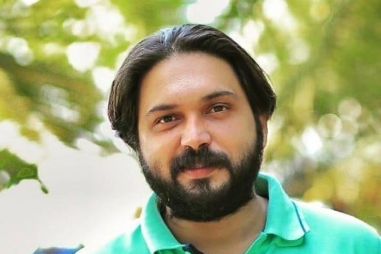Badusha in a green T Shirt with a beard smiles and in the background is a blurred image of tree leaves