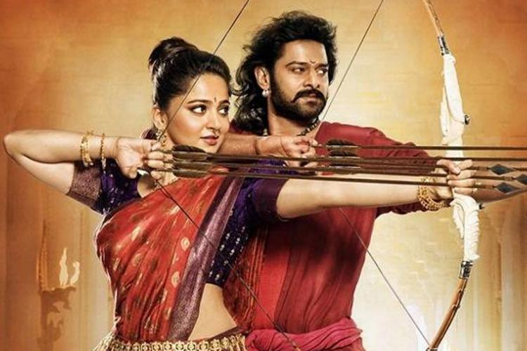 Telugu actors Prabhas and Anushka Shetty dressed in red and holding bows and arrows from a scene in Baahubali The Conclusion