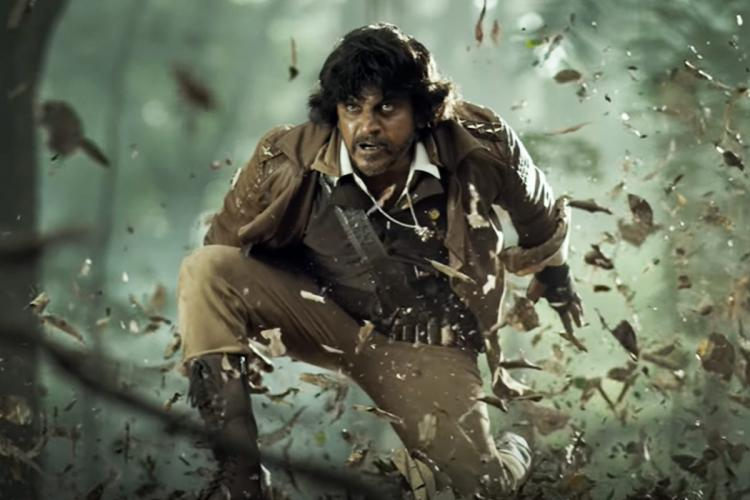 Actor Shivarajkumar is seen in the trailer of Bhajarangi 2 wearing boots and brown shoes and has a wild expression on his face with leaves flying around him all around are trees as he looks like he is in a wooded area