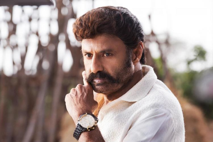 Nandamuri Balakrishna in a white shirt touching his moustache with his left hand