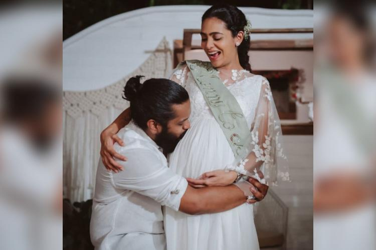 Balu Varghese is seen kissing wife Aileenas baby bump Balu is seen in a white shirt while Aileena is seen in a white dress