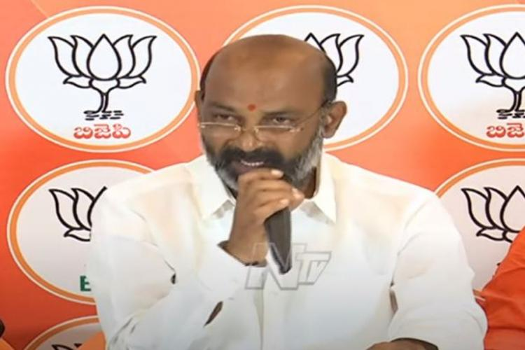 BJP Telangana President Bandi Sanjay in a white shirt addressing media with BJP symbols on the background