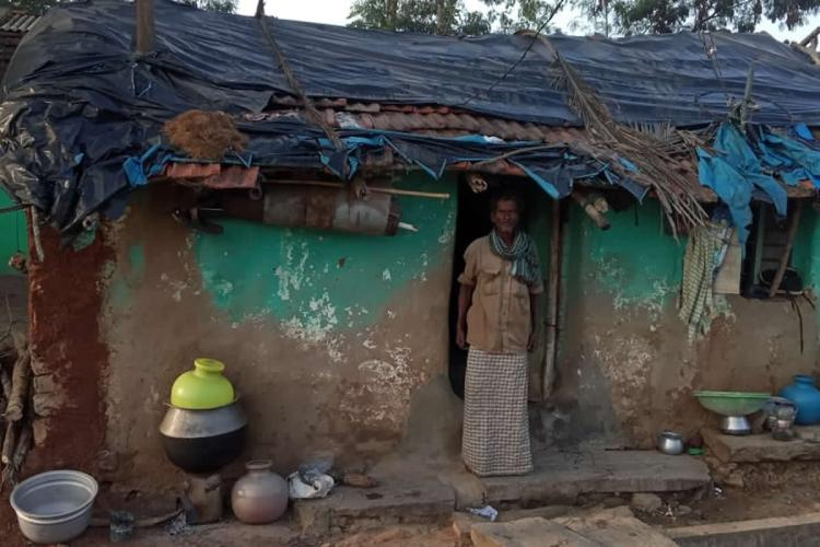 A tribal man wearing a khakhi shirt lungi and a green scarf around his neck standing at the doorway of a hut The tiled roof of the hut is half covered by tarpaulin and some pots and pans can be seen outside the hut