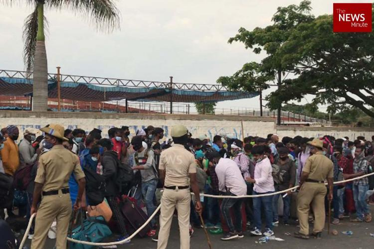 Police officials are seen containing thousands of migrant workers in Bengaluru who have turned up after a message was sent regarding their trains