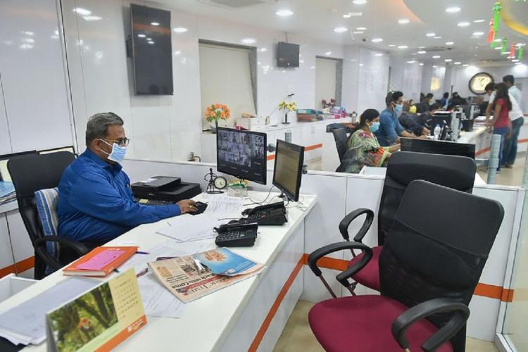 A Bank employee in a blue shirt sitting at his desk at the bank wearing a mask