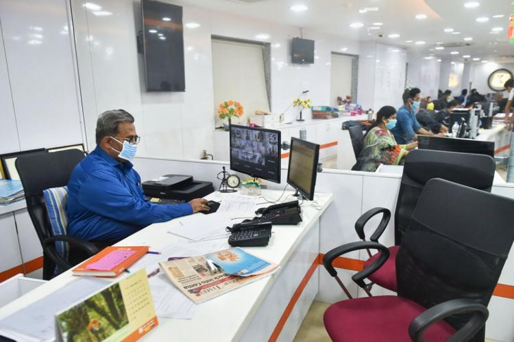 A bank official in a blue shirt sits inside his office and in the distance you can find other employees at their desks