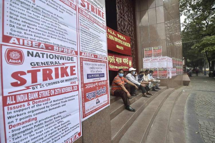 A file photo of a bank strike men sitting in front of a shut bank with posters in focus