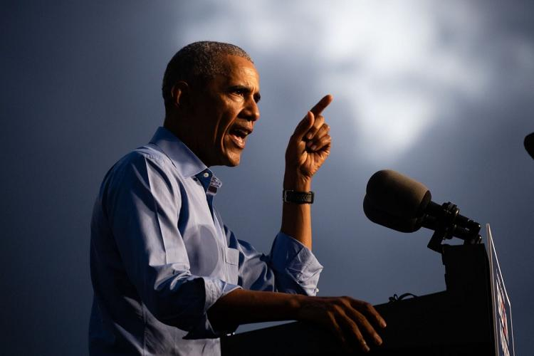 Former US President Barack Obama stands in front of a mic and addresses a crowd