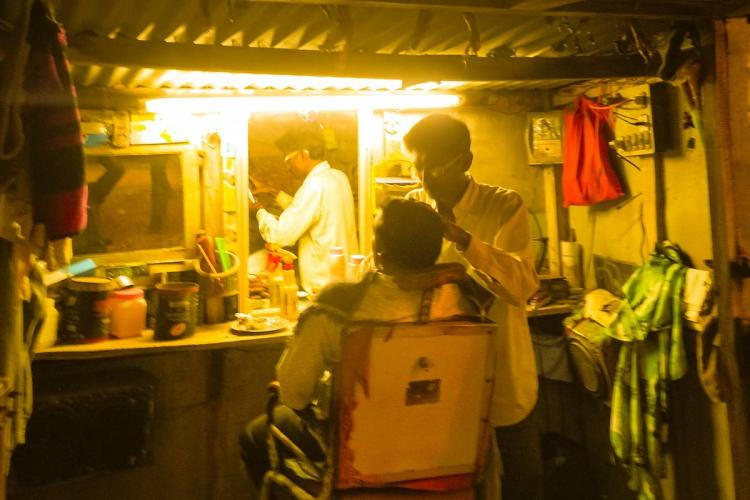In a bright yellow lit barber shop a man attends to a customer
