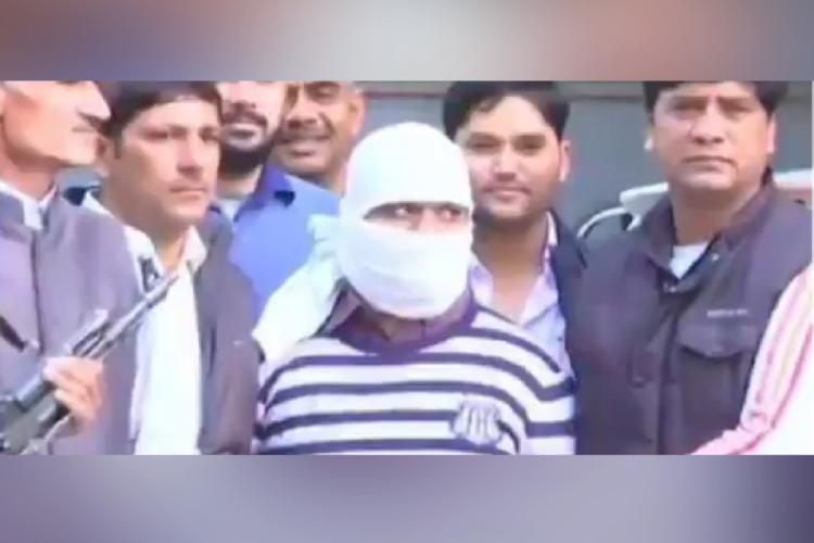 Ariz Khan convict in the Batla House encounter case seen with a white cover on his face flanked by officials