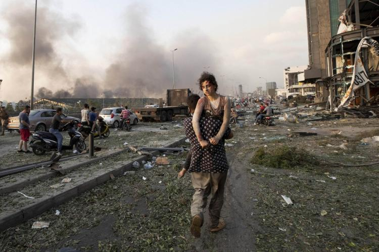 In the aftermath of the massive explosion in Beirut building vehicles have been destroyed A man is seen carrying an injured girl on his shoulder A few men can be seen near the blast site