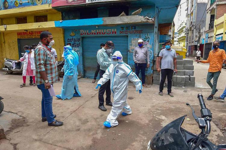 Person wearing oversized personal protective in a bengaluru residential area walks while people wearing masks watch and keep a safe distance