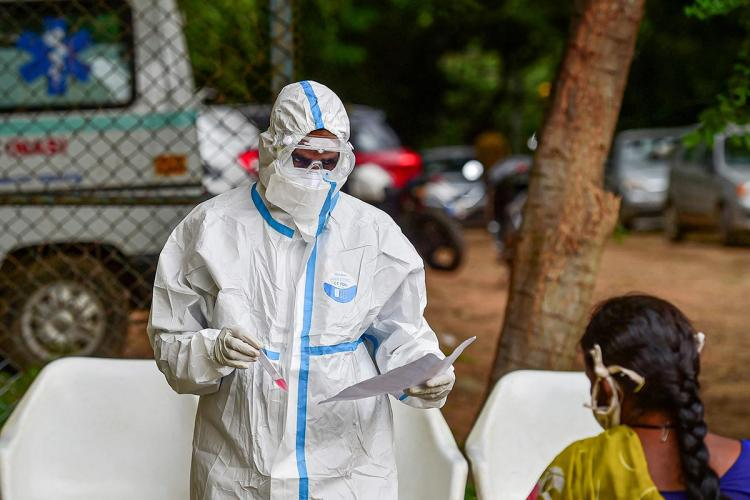 A health worker in a PPE kit is seen taking the samples of a woman in a saree An ambulance is seen in the background