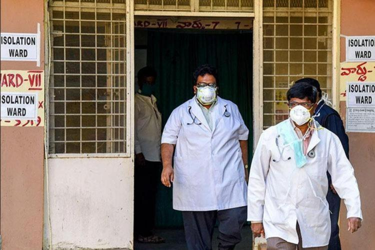 Two people with masks on on walking out of a COVID ward