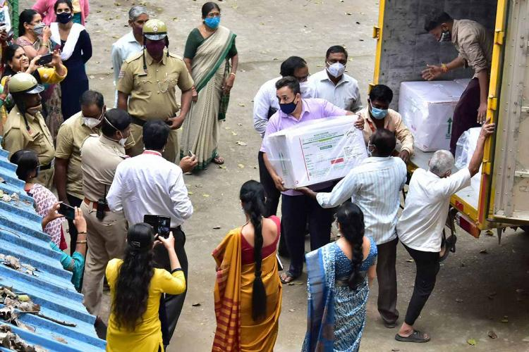 Boxes of Serum Institutes Covishied vaccine arrive in Bengaluru Police personnel and other health members are standing near the storage facility as the boxes are being unloaded from the truck