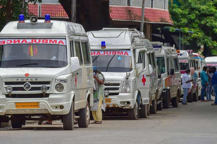 Image shows a line of white ambulances parked on the side of a road in Bangalore