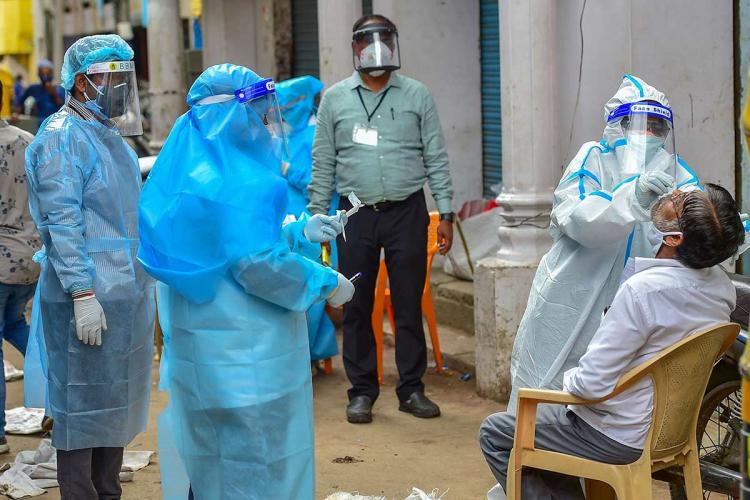 A health worker in a PPE suit collecting sample from a man for coronavirus test