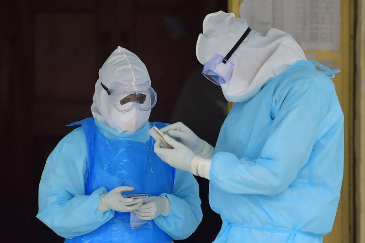 Two heath workers wearing protective equipment looking into one of their phones