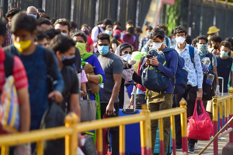 Passengers stand in a queue at a railway station to board the special train to New Delhi