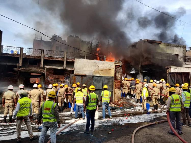 File photo of the fire at Bengalurus Renuka Chemical Godown showing several police and fire personnel looking at the fire