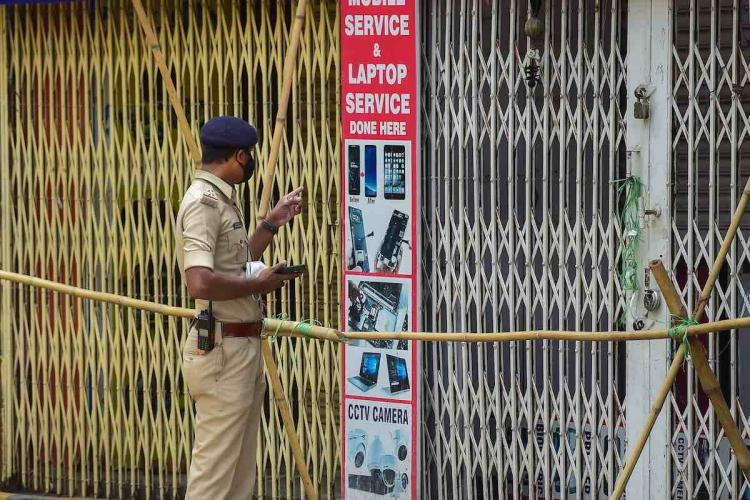 A policeman ensures closure of shops at Sadar Patrappa road locality as Karnataka government announced the area under lockdown after detection of several clusters of coronavirus infections
