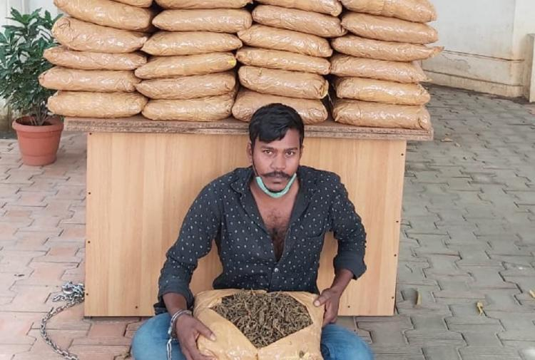 Bengaluru ganja dealer sitting with a big bag of ganja Behind him is a table which has brown bags containing ganja