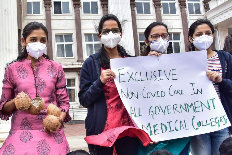 Four medical students in Bengaluru wearing masks hold a protest banner that reads 'Exclusive non-covid care in all government medical colleges