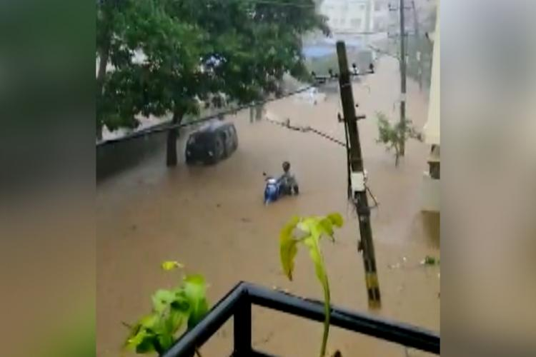 Floods in part of Bengaluru after heavy rains on Octover 23 picture shows a man pushing his scooter in waist deep water