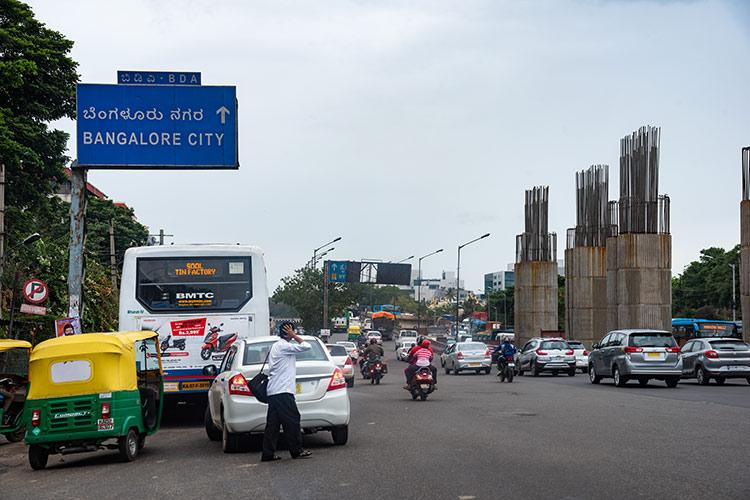 auto bus cars and scooters are seen on a Bengaluru road waiting at a traffic signal