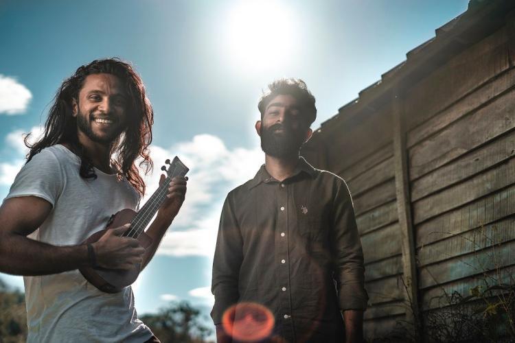 Vishnu with a ukulele and Amal stand against the morning sun