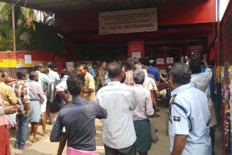 People waiting to buy liquor outside a Bevco Outlet in Kerala