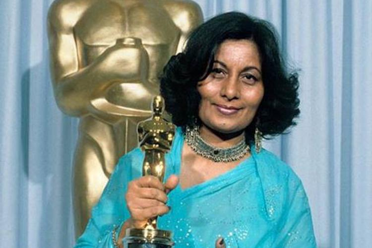 Costume designer Bhanu Athaiya wearing a blue saree and holding her Oscar smiling into the camera