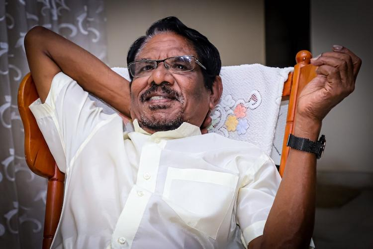 Bharathiraja in white shirt on a reclining chair holdind his hand up