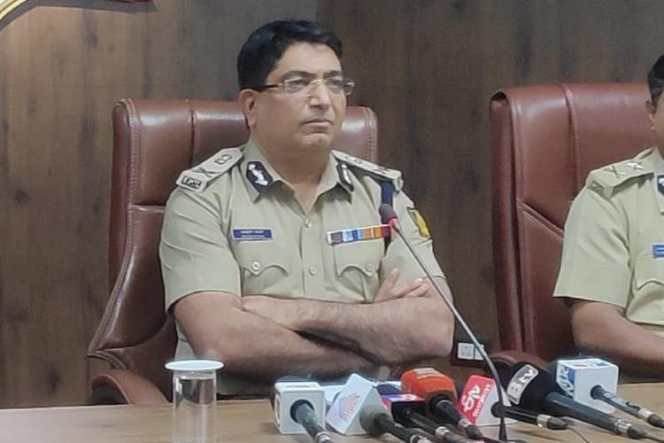 File photo of Bangalore Police commissioner Bhaskar Rao seated in uniform with his arms folded during a press conference there are several news channels mics place in front of him on a table