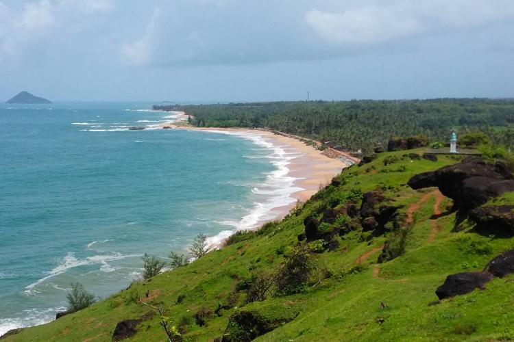 The blue sea meeting the lush green shore at Bhatkal in Karnataka