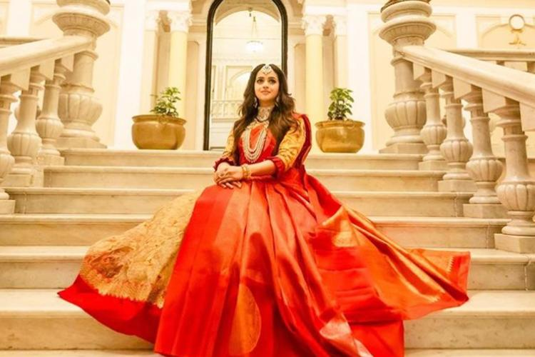 Bhavana wearing a red and gold saree and sitting on a grand staircase