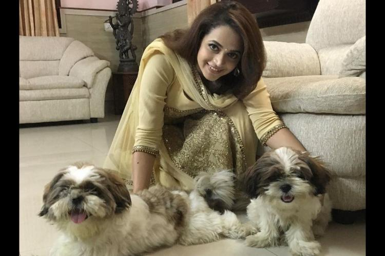 Bhavana in a pale yellow salwar bends down to pet her puppies indoors