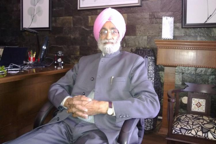 Bhupinder Singh Mann in a dark blue suit and pink turban reclining in a chair