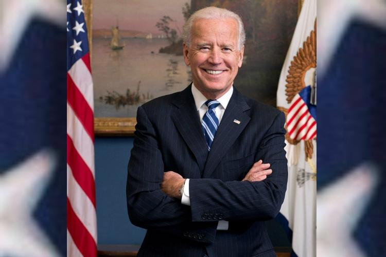 Joe Biden with his arms crossed and the US flag on the left