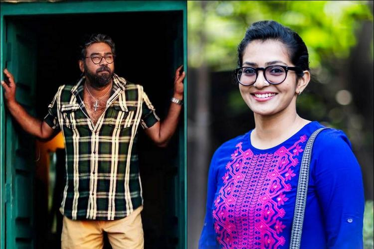 Biju Menon in a black and white check shirt looks out of a door while Parvathy in a blue and pink kurtha and specs smiles