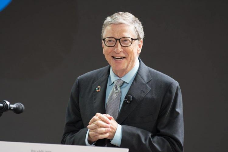 Bill Gates standing the podium and speaking He is wearing a black blazer over a blue shirt and a tie He is smiling in the image