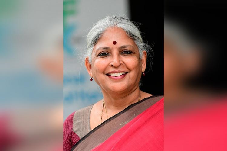 Bina Paul is bright red Sari greyish hair a big bindi smiles
