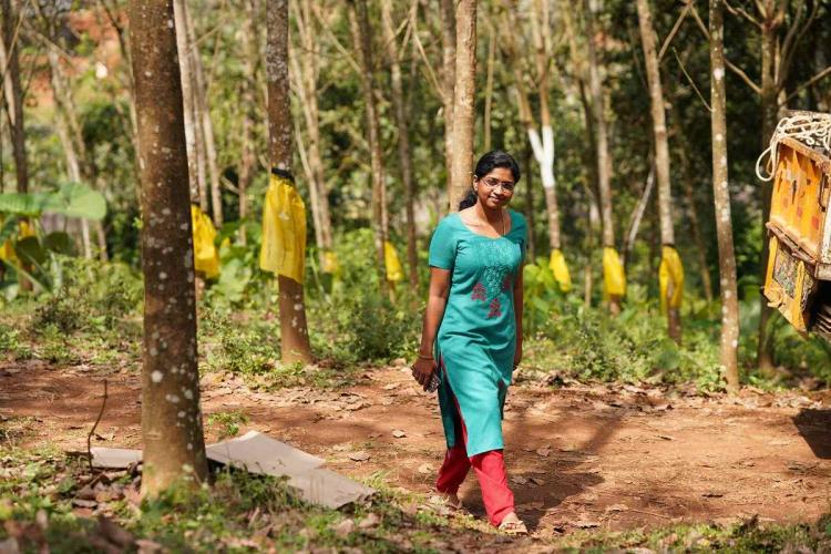 Unnimaya in a blue-green kurthi and red bottom walk among the woods