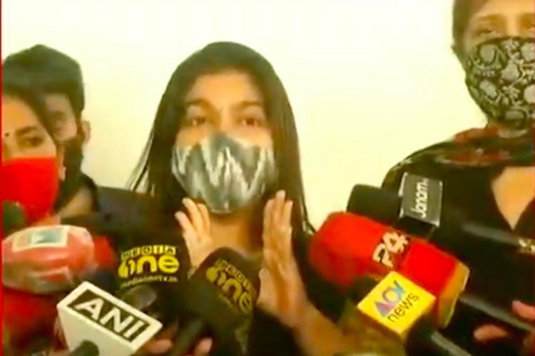 Bineesh Kodiyeris wife Renita in a mask talking to media