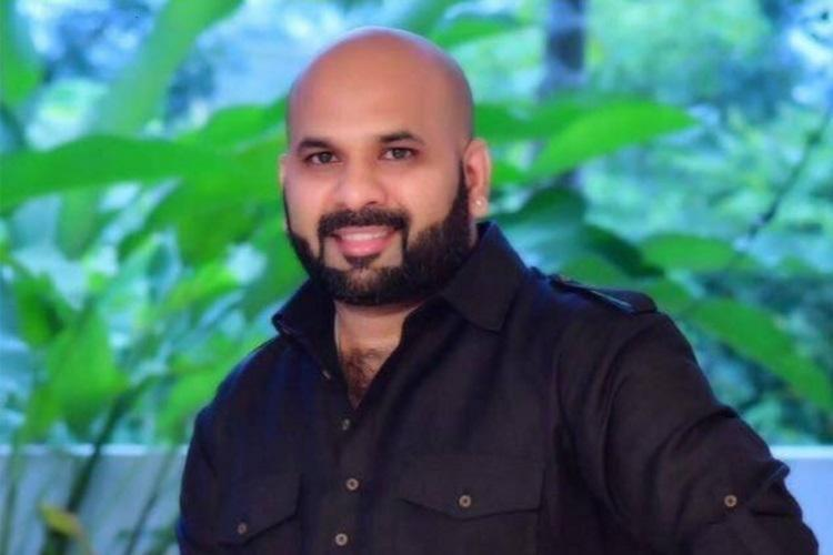 Binoy Kodiyeri in a black shirt is clean shaven has a beard and smiles standing against some plants in the background
