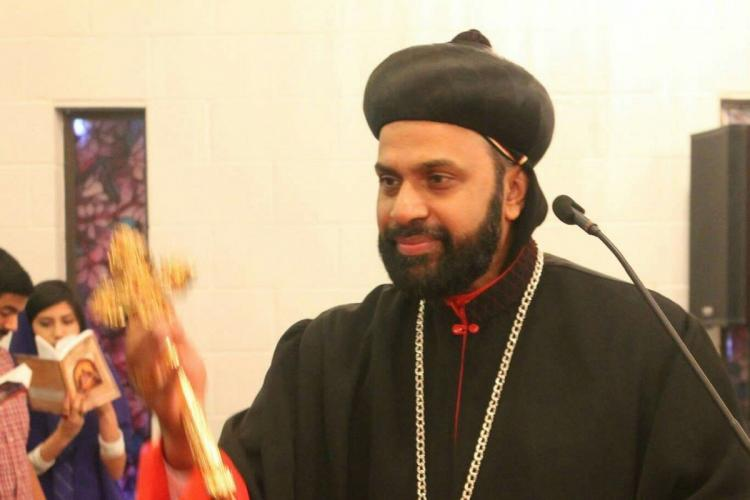 Bishop Kuriakose Mor Theophilos in black robes holding a golden cross in his right hand and standing near a microphone