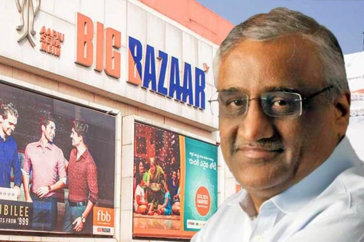 Kishore Biyani next to the logo of his retail business big bazaar