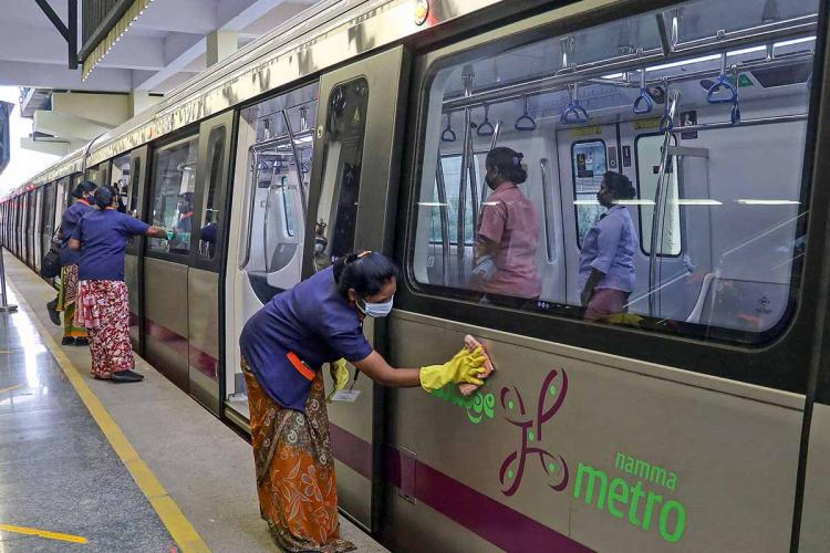 Sanitary staff disinfect the Bengaluru metro train at a station, wearing masks and gloves