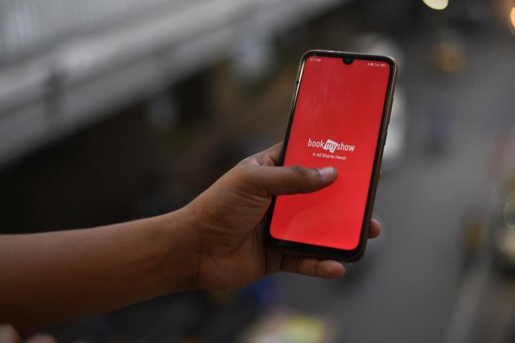 A person holding up a phone from a balcony with the BookMyShow splash screen open