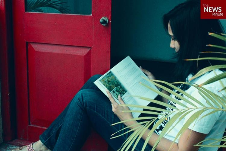 Profile of a woman seated on the floor reading a book She is wearing blue jeans and a white t-shirt A door painted dark brown is seen beside her
